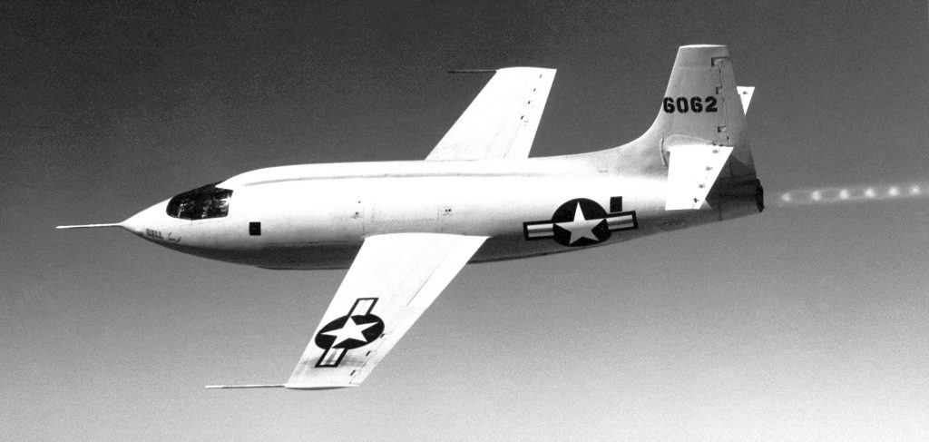 The Bell Aircraft Corporation X-1-1 (#46-062) in flight. The shock wave pattern in the exhaust plume is visible. The X-1 series aircraft were air-launched from a modified Boeing B-29 or B-50 Superfortress bombers.