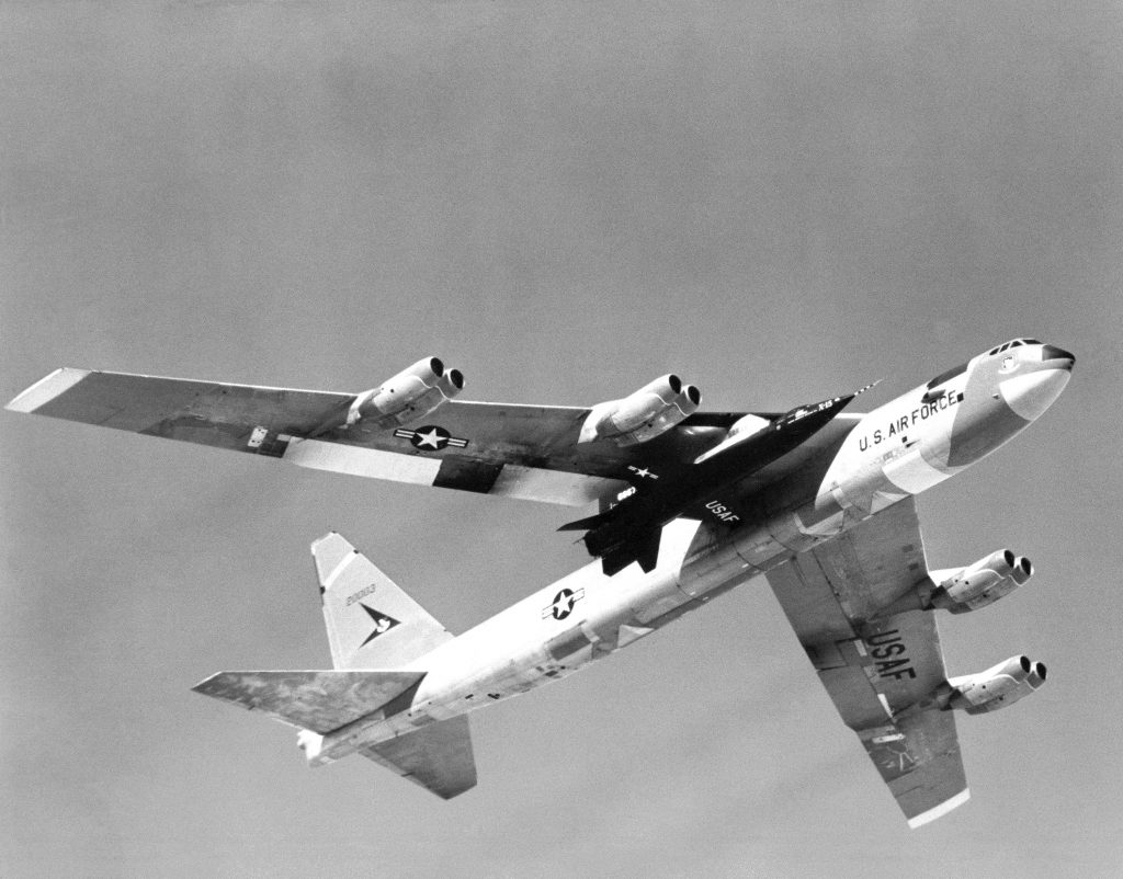 One of three X-15 rocket-powered research aircraft being carried aloft under the wing of its B-52 mothership. The X-15 was air launched from the B-52 so the rocket plane would have enough fuel to reach its high speed and altitude test points. For flight in the dense air of the usable atmosphere, the X-15 used conventional aerodynamic controls. For flight in the thin air outside of the appreciable Earth's atmosphere, the X-15 used a reaction control system. Hydrogen peroxide thrust rockets located on the nose of the aircraft provided pitch and yaw control. Those on the wings provided roll control. The X-15s made a total of 199 flights over a period of nearly 10 years and set world's unofficial speed and altitude records of 4,520 miles per hour (Mach 6.7) and 354,200 feet. Information gained from the highly successful X-15 program contributed to the development of the Mercury, Gemini, and Apollo manned spaceflight programs and also the Space Shuttle program.